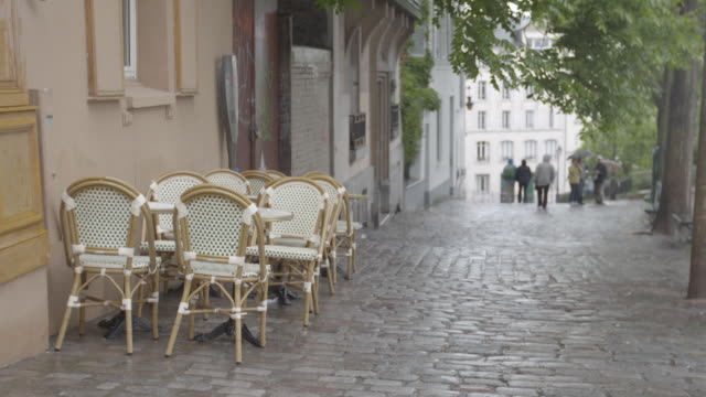 Shot of wicker chairs and tables on a cobbled street in Paris, France