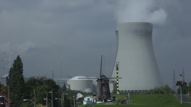 MS Shot of windmill and nuclear power plant / Doel, Belgium