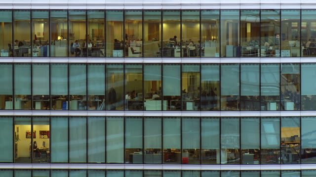 ms t/l shot of windows of office block of people at work / london, united kingdom  - office block exterior stock-videos und b-roll-filmmaterial