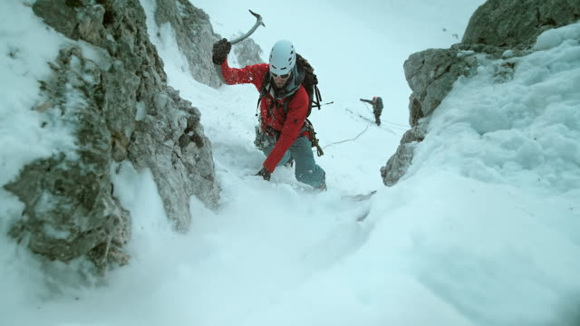 LD shot of winter climbers climbing in harsh conditions