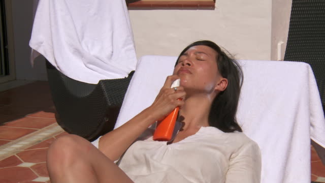 ms shot of woman applying sunscreen on this face / marbella, andalusia, spain - sonnencreme stock-videos und b-roll-filmmaterial