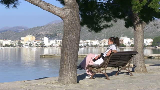stockvideo's en b-roll-footage met ms shot of woman at seaside promenade / puerto pollenca, mallorca, spain - alleen één mid volwassen vrouw