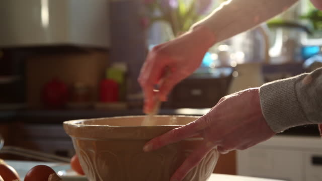 CU TU TD Shot of woman breaking eggs in bowl sieving flour and mixing / London, Greater London, United Kingdom