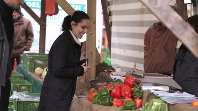ms tu pan shot of woman buying vegetables, pepper, from market vendor / potsdam, brandenburg, germany  - bell pepper stock videos & royalty-free footage