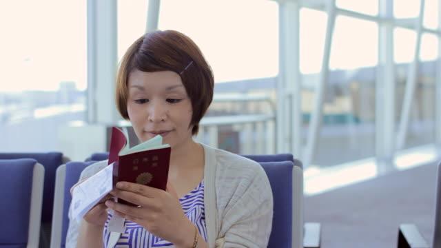 CU PAN Shot of woman checking her passport at the airport / Hong Kong, China
