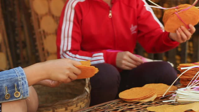 MS SLO MO Shot of woman counting cassava crackers / Luang Prabang, Laos