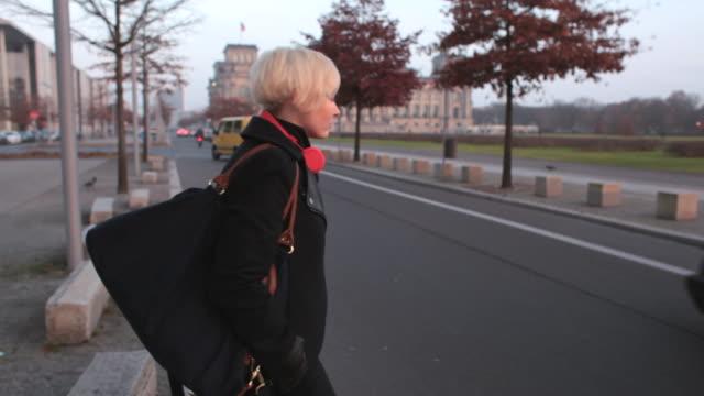 vidéos et rushes de ms ts shot of woman crossing street and walking towards reichstag building / berlin, germany  - bâtiment du parlement