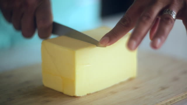 cu shot of woman cutting block of butter on wooden kitchen board / auckland, new zealand - butter stock videos & royalty-free footage