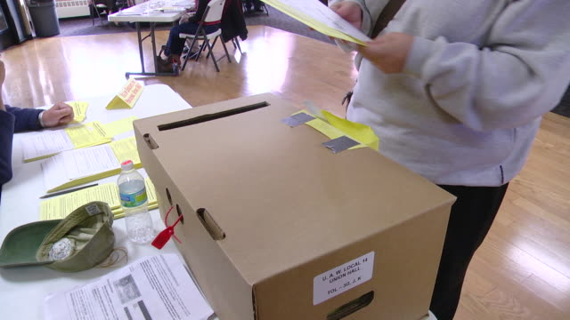 CU Shot of woman deposits provisional ballot in ballot box when voting at union hall / Toledo, Ohio, United States