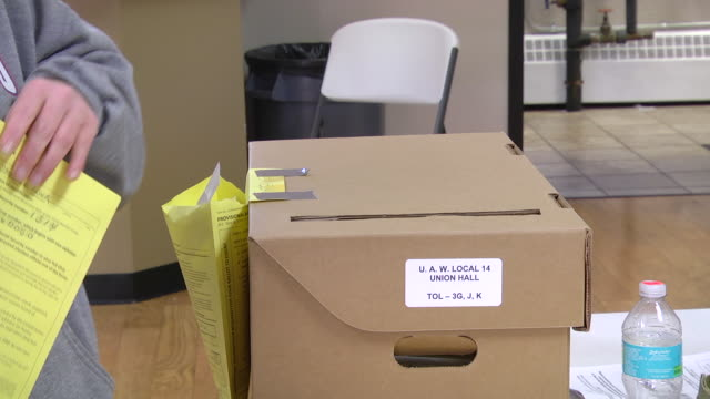 cu shot of woman deposits provisional ballot in ballot box when voting at uaw hall / toledo, ohio, united states - ballot box stock videos & royalty-free footage