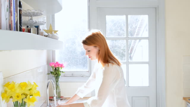MS Shot of woman drinking glass of water in kitchen / London, Greater London, United Kingdom