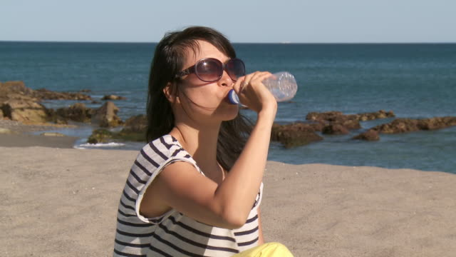 ms shot of woman drinking water at beach / marbella, andalusia, spain - cold drink stock videos and b-roll footage