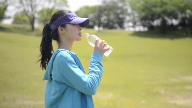 vidéos et rushes de ms shot of woman drinks water in jogging wear / uji, kyoto, japan  - drinking