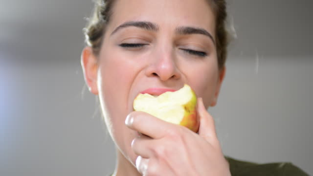 stockvideo's en b-roll-footage met cu shot of woman eating apple / london, greater london, united kingdom - bijten