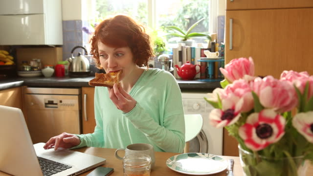 MS Shot of Woman eating breakfast while working on computer in kitchen at home / London, United Kingdom