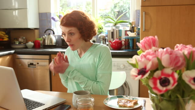 ms shot of woman eating breakfast while working on computer in kitchen at home / london, united kingdom - redhead stock videos & royalty-free footage