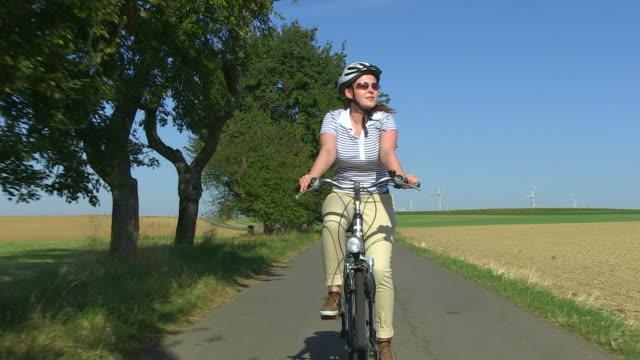 ms shot of woman enjoying cycling with bikes and helmets through farmfield / merzig, saarland, germany - windenergie stock-videos und b-roll-filmmaterial