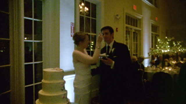 MS Shot of Woman feeds man cake at wedding reception / New York, United States