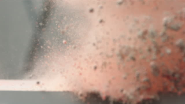 CU SLO MO Shot of woman hand as it brushes through pile of colored dust sending it in to air / United Kingdom