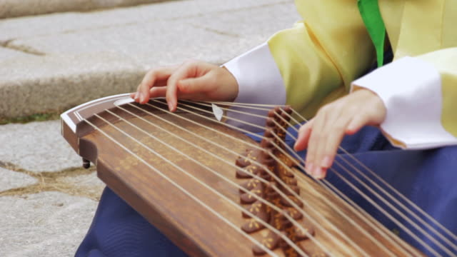CU Shot of Woman hands playing gayageum ( traditional Korean zir-like string instrument) / Yongin, Gyeonggido, South Korea