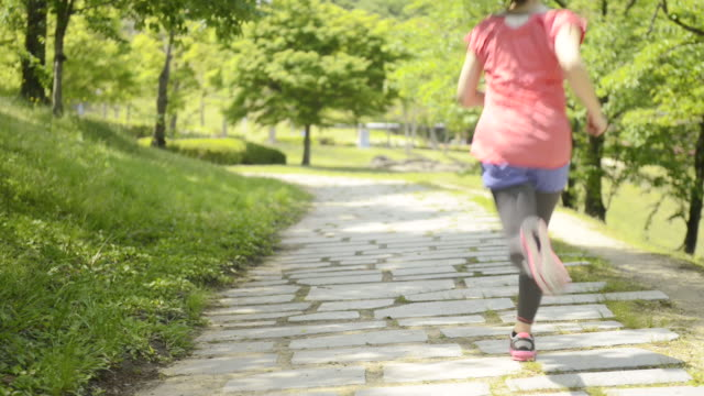 ms shot of woman having jogging in park / uji, kyoto, japan  - 移動中点の映像素材/bロール