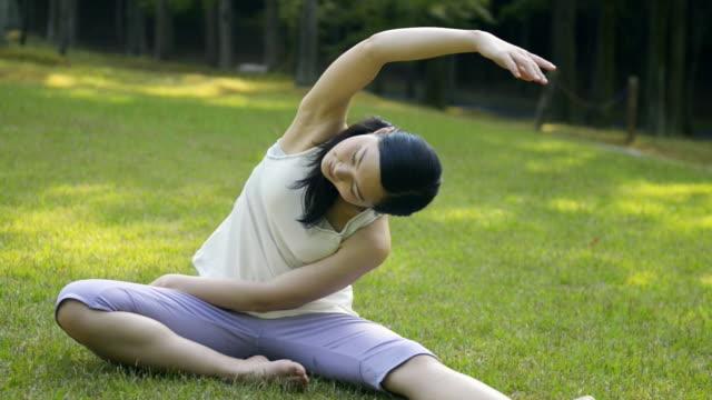 vídeos y material grabado en eventos de stock de ms shot of woman having stretch of lawn in park / joyo, kyoto, japan - brazo humano
