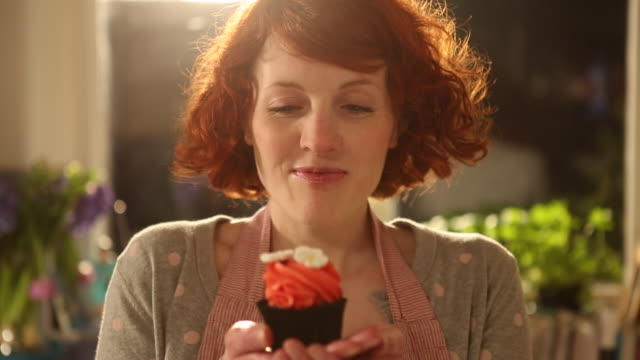 cu shot of woman holding up cupcake and smiling / london, greater london, united kingdom - greater london video stock e b–roll