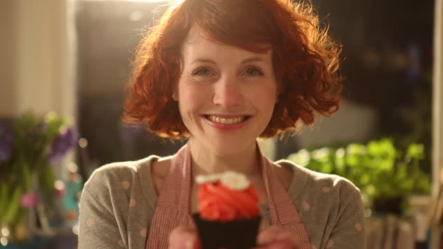 cu shot of woman holding up cupcake and smiling / london, greater london, united kingdom - selbstgemacht stock-videos und b-roll-filmmaterial