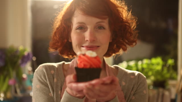 cu r/f shot of woman holding up cupcake and smiling / london, greater london, united kingdom - cupcake stock videos & royalty-free footage