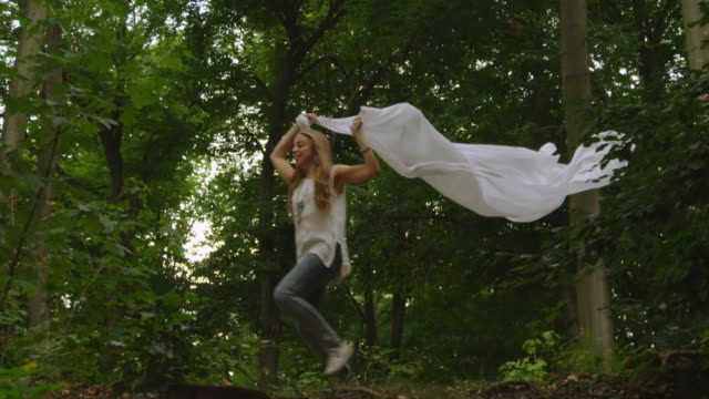 """""""WS SLO MO Shot of Woman holding white sheet while running in forest / Berlin, Germany"""""""