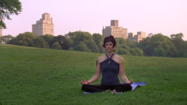MS Shot of woman in Prospect Park doing Auspicious Pose Yoga position / New York, United States