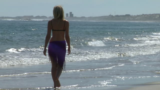 ms tu ts shot of woman in sarong and bikini walking along shoreline / north west province, south africa - sarong stock videos and b-roll footage