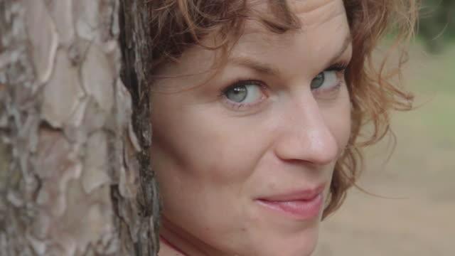 vidéos et rushes de ecu pan shot of woman in wood turns and smiles / london, united kingdom - cheveux bruns