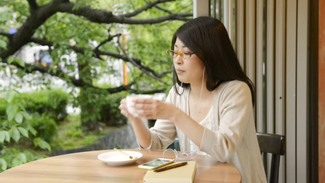 MS Shot of woman is drinking coffee while listening to music in café / Kyoto, Japan