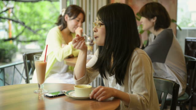 ms shot of woman is eating sweets happily in cafã© / kyoto, japan - カフェテリア点の映像素材/bロール