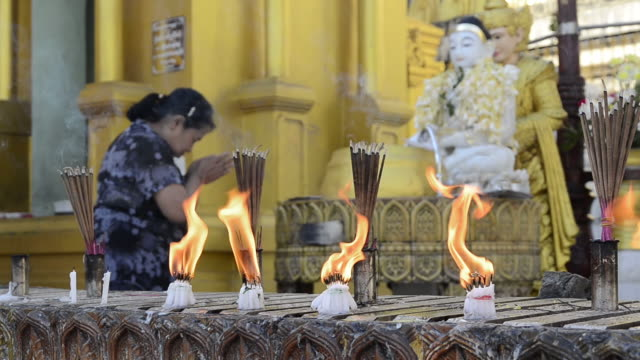 Ms Shot Of Woman Is Praying In Front Of Buddha Likeness And Candles