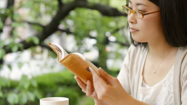 CU Shot of woman is reading book in café / Kyoto, Japan