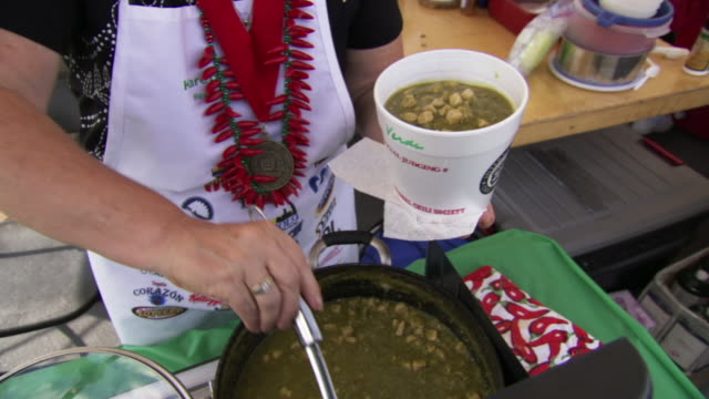 ms zo shot of woman ladles chili verde into big cup during worlds championship chili cook off / omaha, nebraska, united states - chilli con carne video stock e b–roll
