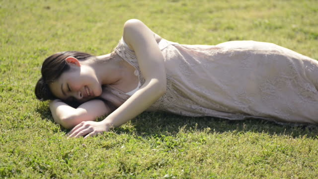 ms shot of woman lies at lawn in park and relaxing / uji, kyoto, japan  - auf der seite liegen stock-videos und b-roll-filmmaterial