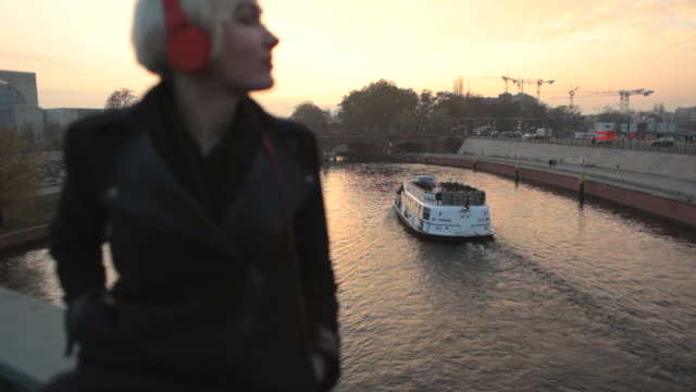 ms r/f shot of woman listening to music at sunset on bridge over river spree with german chancellery in background / berlin, germany   - short hair stock videos & royalty-free footage