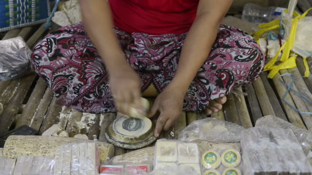 CU Shot of woman makes tanaka paste for skin cosmetics on nyaung u market / Bagan, Mandalay Division, Myanmar
