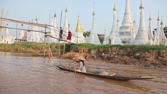 ms pov shot of woman on boat on river (white temples to right) passing through bridge / inle lake, shan state, myanmar    - shan state stock videos & royalty-free footage