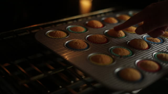 cu shot of woman opening oven door and testing to check if cupcakes are baked with light finger prod / auckland, new zealand - ofen stock-videos und b-roll-filmmaterial