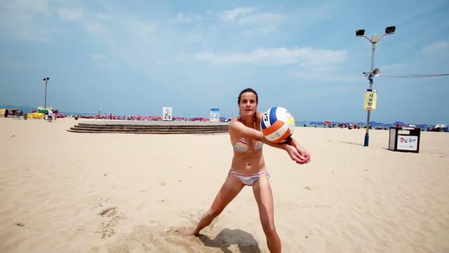 stockvideo's en b-roll-footage met ms shot of woman playing beach volleyball at sandy beach / boryeong, chungcheongnamdo, south korea  - zonnescherm gefabriceerd object