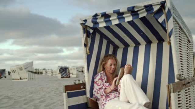 ms shot of woman playing with tablet sitting on beach chair at beach / st. peter ording, schleswig holstein, germany  - deutsche nordseeregion stock-videos und b-roll-filmmaterial