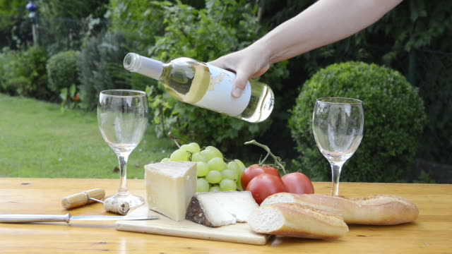 ms shot of woman pouring glasses of white wine at picnic with cheese, bread, tomatoes and grapes / siena, tuscany, italy - wine stock videos & royalty-free footage