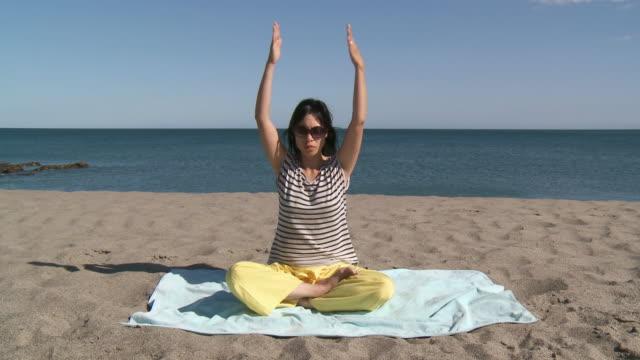 vídeos de stock, filmes e b-roll de ms shot of woman practicing yoga on beach / marbella, andalusia, spain - toalha de praia