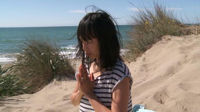 vídeos de stock, filmes e b-roll de cu shot of woman practicing yoga on dune / marbella, andalusia, spain - toalha de praia