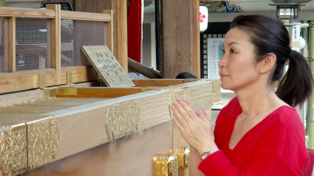 ms shot of woman praying at yushima shrine / tokyo, japan - shrine stock videos and b-roll footage