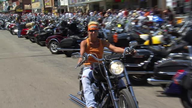 vídeos y material grabado en eventos de stock de ms zo pan shot of woman riding along main street during sturgis motorcycle rally / sturgis, south dakota, united states - cinta de cabeza